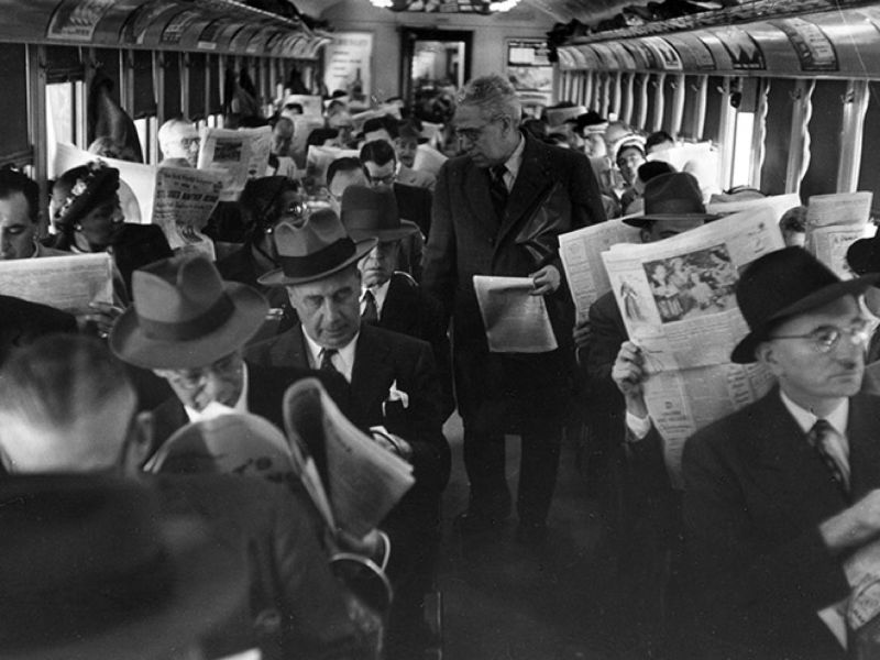staring at newspapers on a train
